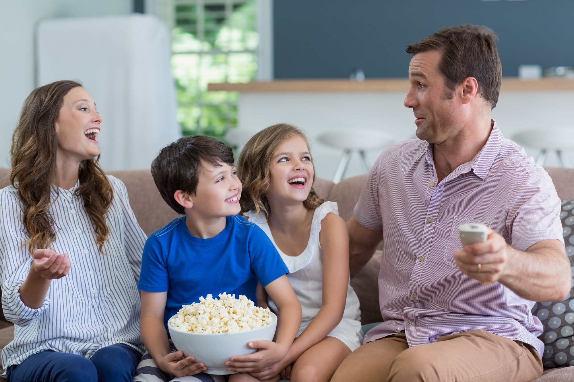 Family watching tv and eating popcorn in living room at home